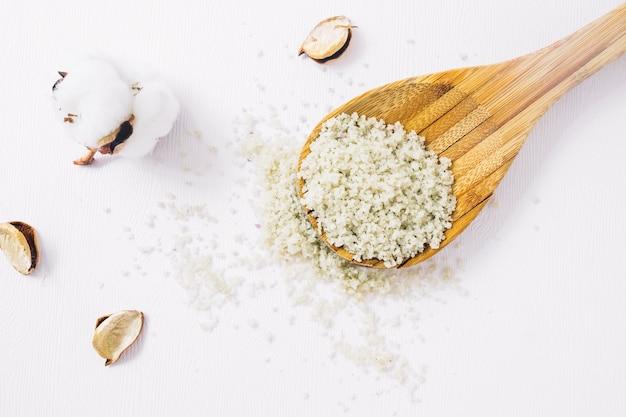 Il bocciolo di cotone e il corpo fatto in casa scrub su mestolo di legno su sfondo bianco