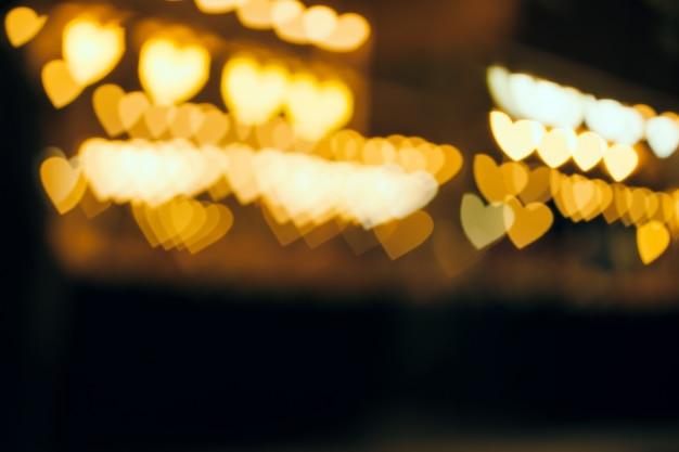 Il bokeh sfocato del cuore d'oro forma dalla linea di luce nella notte al negozio di strada