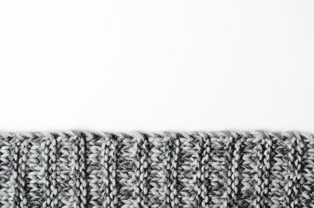 Il bordo di un plaid in maglia grigia su sfondo bianco