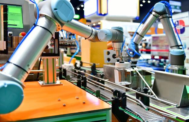 Il braccio del robot ha sistemato la bottiglia di acqua di vetro sull'attrezzatura automatica del macchinario industriale nella linea di produzione fabbrica