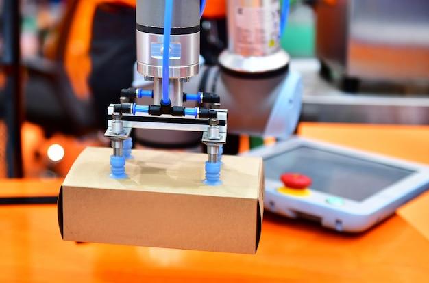 Il braccio del robot ha sistemato la scatola del prodotto sull'attrezzatura automatica del macchinario industriale nella fabbrica della linea di produzione