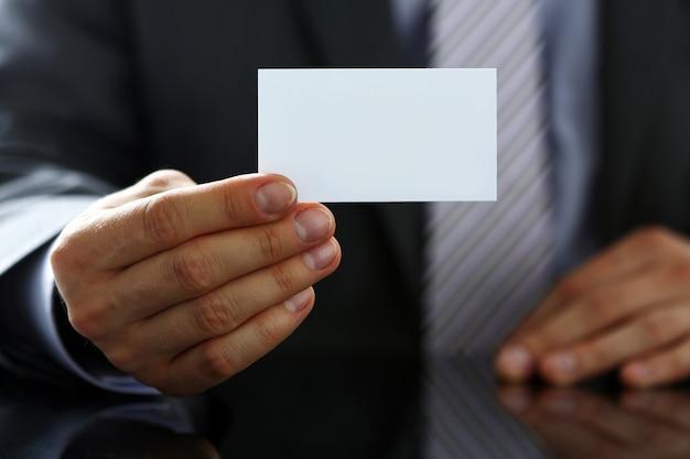 Il braccio maschile in tuta dà un biglietto da visita in bianco al visitatore