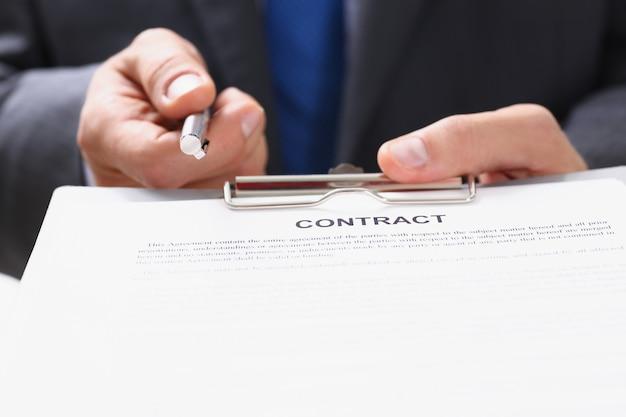 Il braccio maschile in tuta offre il modulo di contratto