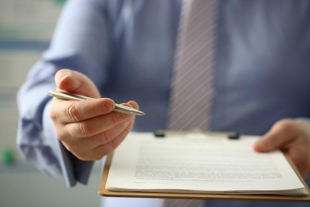 Il braccio maschile in tuta offre la forma di contratto negli appunti