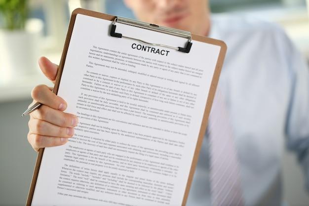 Il braccio maschile in tuta offre un modulo di contratto