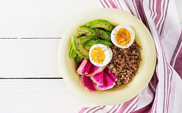 Il buddha del grano saraceno lancia le ciotole con l'avocado, le uova sode e il ravanello dell'anguria sulla tavola bianca.