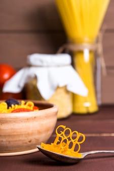 Il buon cibo è allineato con la pasta su un cucchiaio vicino a un piatto con pasta pronta