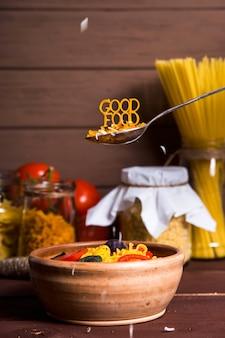 Il buon cibo è foderato di pasta su un cucchiaio vicino a un piatto