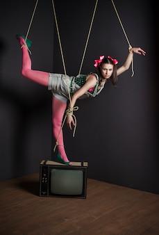 Il burattino della donna sulla tv con le sue mani ha legato la posa