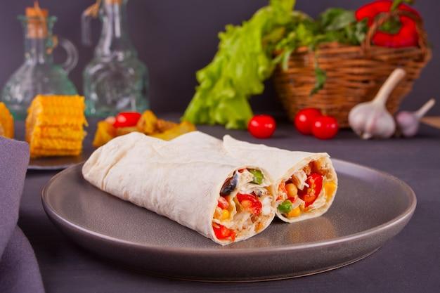 Il burrito rotola con le verdure sulla tavola e le verdure nere, i pomodori ciliegia e l'aglio a fondo
