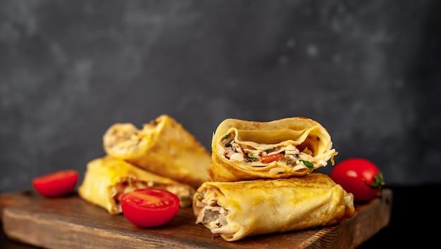Il burrito si avvolge con pollo e verdure, su uno sfondo di cemento, shawarma messicano