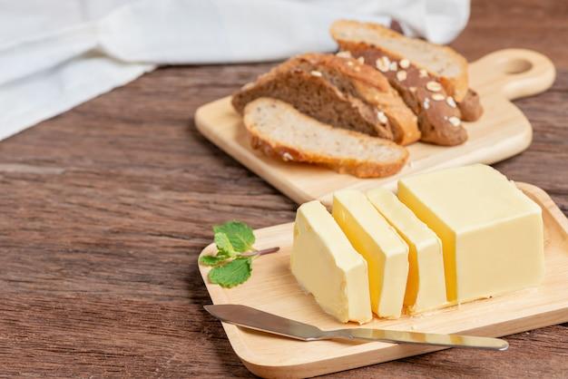 Il burro fresco ha tagliato con la lama sulla zolla e sul pane di legno.