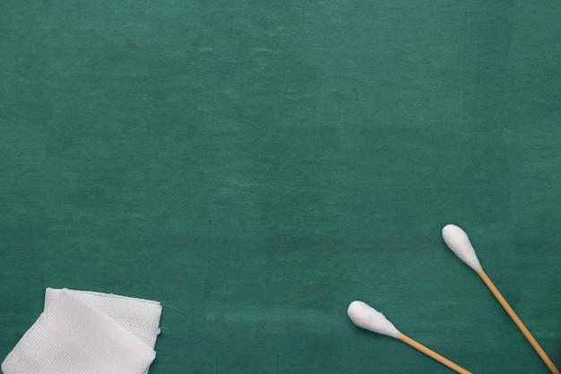 Il bus di cotone del tampone e della garza attacca sul vestito chirurgico medico verde con lo spazio della copia