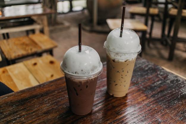 Il cacao e il caffè ghiacciati in plastica sono serviti sulla tavola di legno.