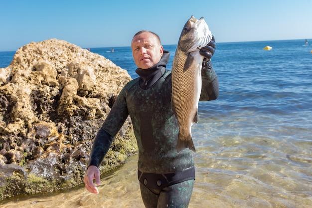 Il cacciatore subacqueo mostra la cattura. robalo portoghese.