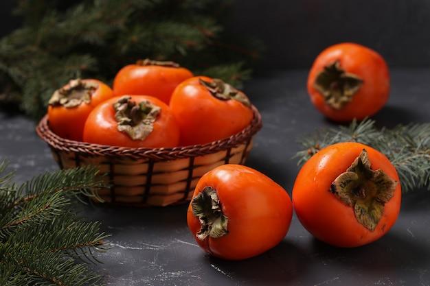 Il cachi arancio maturo fruttifica su una tavola e in un canestro di vimini, l'orientamento orizzontale, primo piano