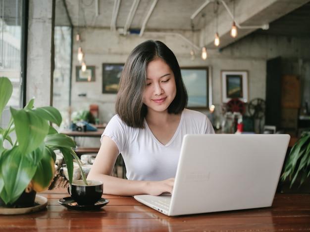 Il caffè bevente della donna asiatica e si rilassa nel caffè della caffetteria