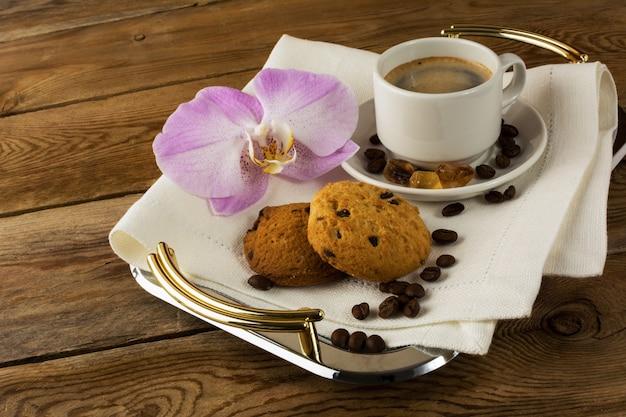 Il caffè è servito con l'orchidea sul vassoio da portata