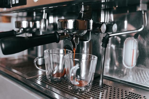Il caffè espresso fragrante scorre da una macchina da caffè in una tazza.