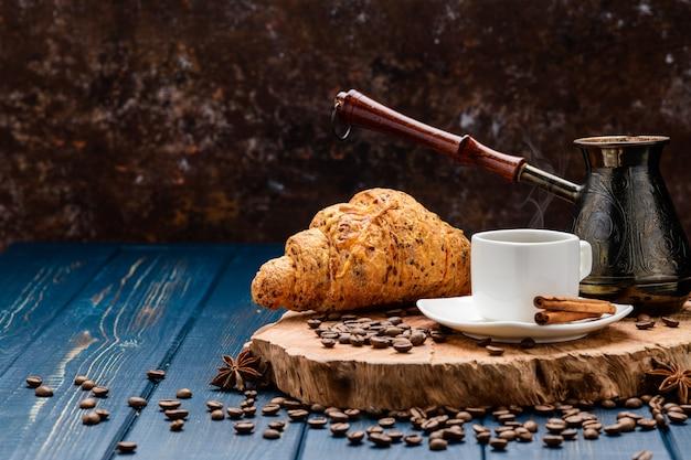 Il caffè si versa in una tazza su un tavolo di legno blu con chicchi di caffè e un cornetto