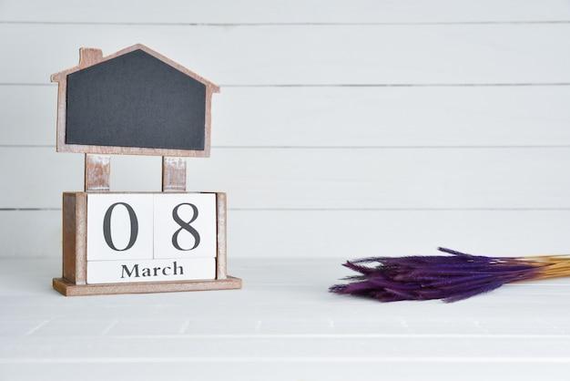 Il calendario di legno del blocchetto del testo dell'8 marzo con la porpora ha asciugato il fiore su fondo di legno bianco.