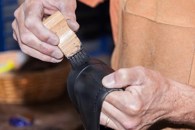 Il calzolaio mette il lucido da scarpe
