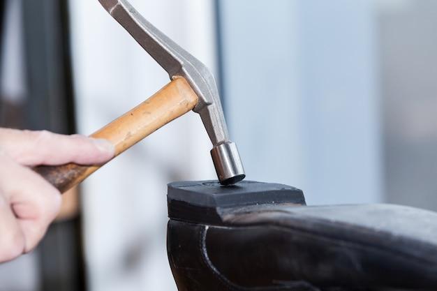 Il calzolaio ripara una scarpa