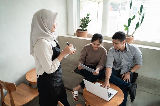 Il cameriere della donna hijab scrive l'ordine del cliente