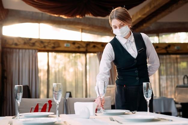 Il cameriere in una maschera protettiva medica serve il tavolo del ristorante.