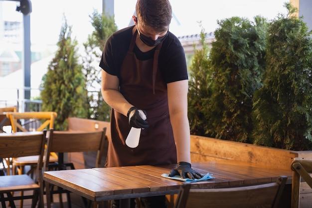 Il cameriere lavora in un ristorante con una mascherina medica, guanti durante la pandemia di coronavirus
