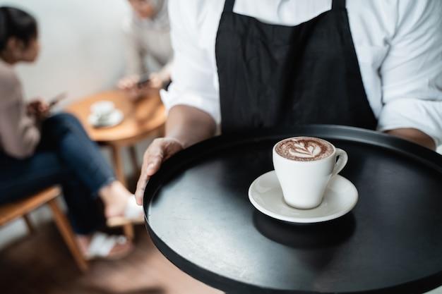 Il cameriere serve una tazza di caffè sul vassoio