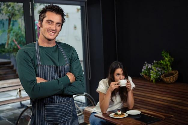 Il cameriere sorridente che posa con le armi attraversa davanti al cliente