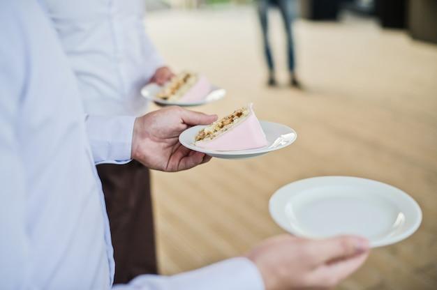 Il cameriere tiene i piatti con pezzi di torta