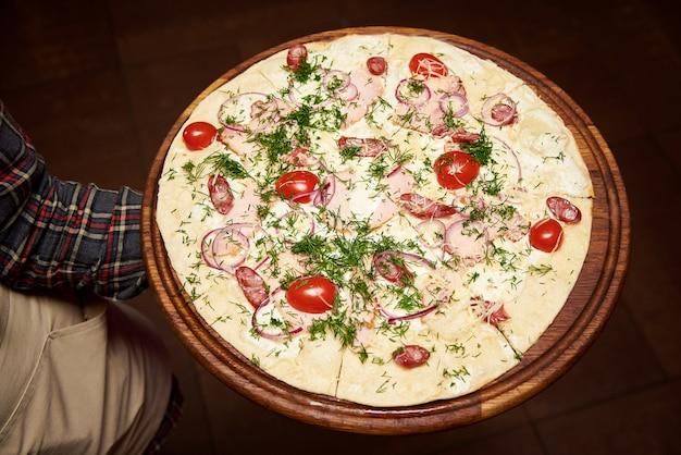 Il cameriere tiene una deliziosa pizza calda sul tavolo