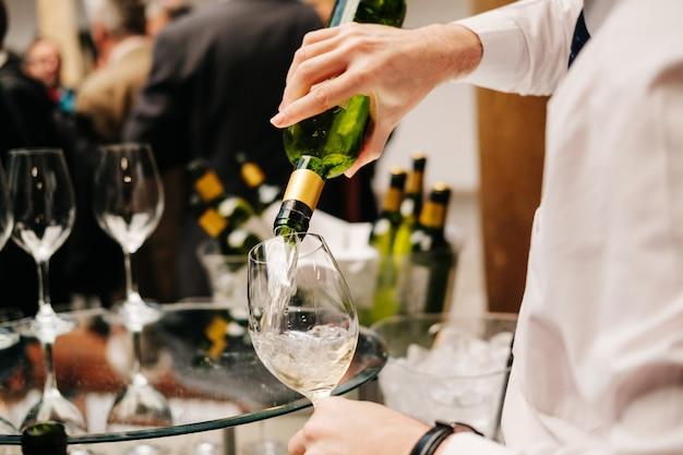 Il cameriere versa il vino da una bottiglia in un bicchiere durante un evento