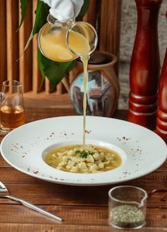 Il cameriere versa l'aceto nella zuppa di gnocchi di dushbara