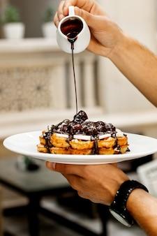 Il cameriere versa la salsa di cioccolato su waffle con frutta