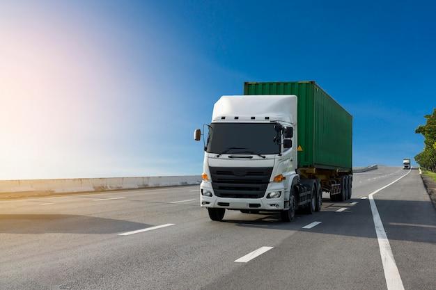 Il camion bianco sulla strada della strada principale con il contenitore verde, importa, trasporta il trasporto logistico
