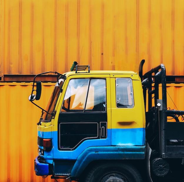 Il camion giallo ha parcheggiato vicino ad un contenitore di contenitore giallo