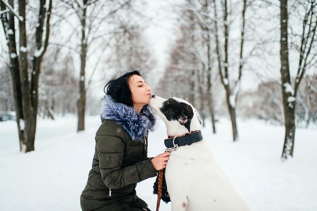 Il cane bacia la sua padrona sulla via nel parco dell'inverno.