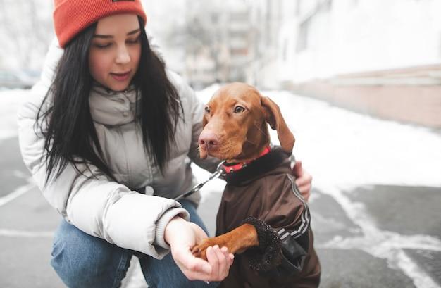 Il cane con i vestiti e la ragazza sono seduti sulla strada invernale
