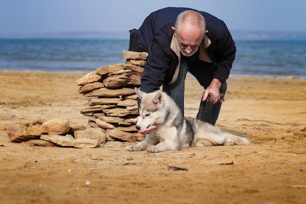 Il cane del husky e dell'uomo cammina nel parco.