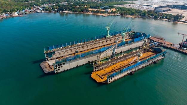 Il cantiere navale di vista aerea ha la macchina della gru e la nave porta-container in oceano nero