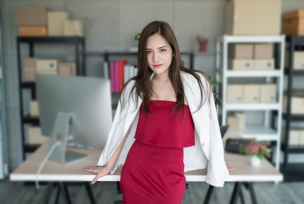 Il capo indossa un vestito rosso e un abito bianco. è sicura che lavora donna e bella.