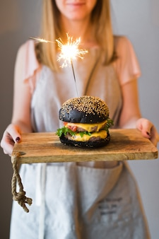 Il capo tiene in mano un tagliere di legno con un hamburger nero.