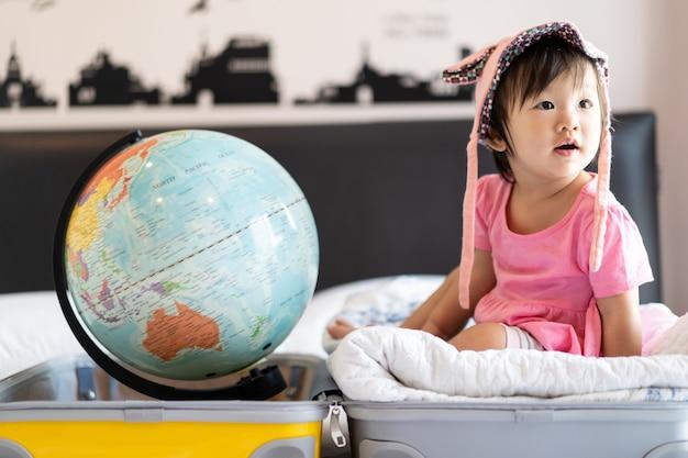 Il cappello d'uso della piccola neonata sveglia asiatica che si siede sulla borsa di viaggio con il sorriso che si sente divertente e che ride sul letto in camera da letto con il globo del mondo ha messo dall'altro lato della borsa della valigia.