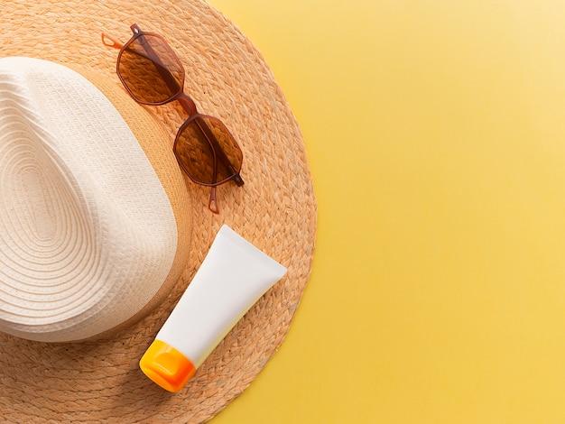 Il cappello della donna della paglia con i vetri di sole e la protezione superiore della crema osservano il fondo giallo luminoso piano.