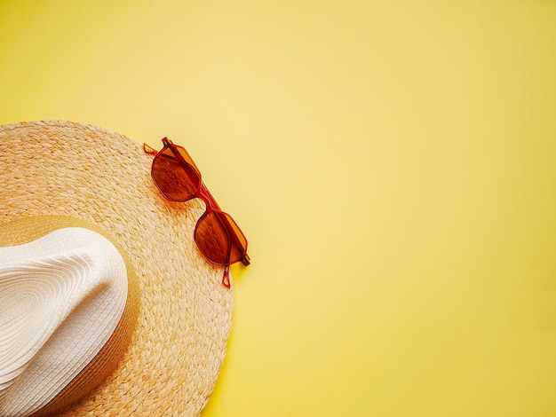 Il cappello della donna della paglia con i vetri di sole superiore osserva la disposizione piana del fondo giallo luminoso singola