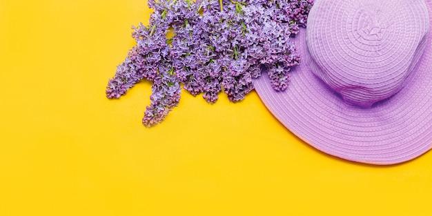 Il cappello estivo rosa da donna e un bouquet di fiori lilla sbocciano