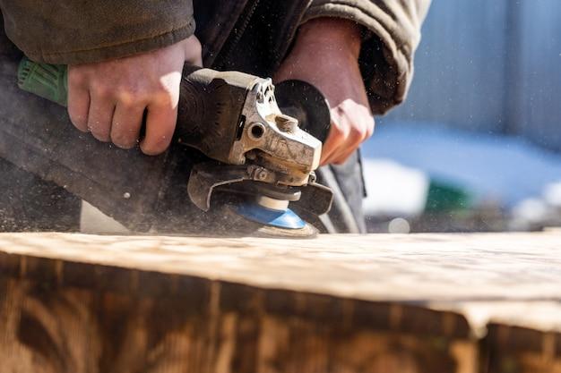 Il carpentiere che lavora macina il legno, rimuovendo la vecchia vernice